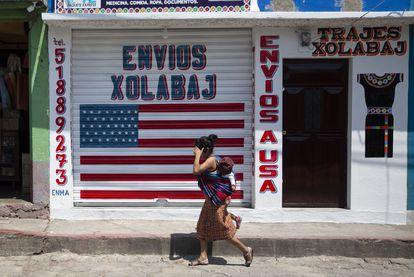 Una mujer pasea con su hijo a cuestas delante de un negocio de envíos y recepción de remesas cerrado en Joyabaj, Guatemala, el pasado 3 de abril.