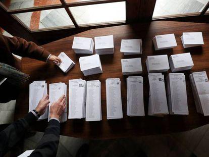 Dos personas escogen papeletas para votar en un centro electoral de Barcelona.