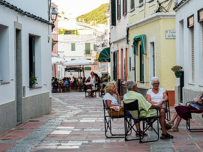 Vecinos de Es Mercadal conversan a la puerta de casa. Al fondo, la plaça de la Constitució.