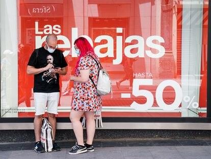Dos personas consultan su teléfono móvil delante de un escaparate con un cartel de rebajas, el 25 de junio en Madrid.