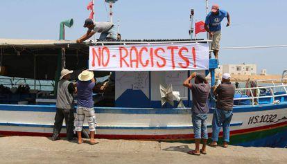 Pescadores tunecinos colocan una pancarta contra el navío anti-migrantes C-Star, este domingo en Zarzis.