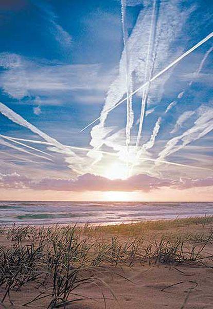 Estelas de aviones entremezcladas con nubes sobre una playa australiana.