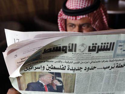 Un hombre lee en Yedda (Arabia Saudí) un periódico que lleva en portada el plan de paz de Trump.