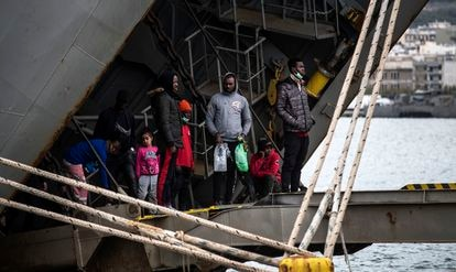 Un grupo de migrantes se asoman al exterior desde un buque griego atracado en el puerto de Mitilene, en la isla de Lesbos. ÁLVARO GARCÍA