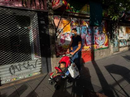 Un hombre pasea a su hijo en el barrio madrileño de Vallecas el 25 de septiembre.