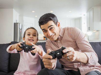 Un padre y su hija juegan a la consola en el salón de casa.