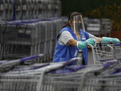 Una mujer desinfecta los carritos del supermercado en Ciudad de México, el 15 de junio.