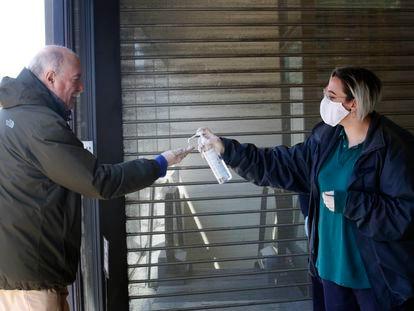Una mujer ayuda a un vecino de Terrassa a desinfectar sus manos.