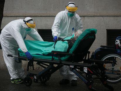Personal sanitario traslada de su vivienda a una anciana contagiada por coronavirus en Barcelona.