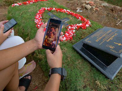 Tirsa Manitik y Erik Alexander muestran la foto de su bebé en un móvil cuando visitan la tumba de su hijo, que dio positivo por covid.19 antes de morir, en el Cementerio de Tegal Alur en Yakarta.