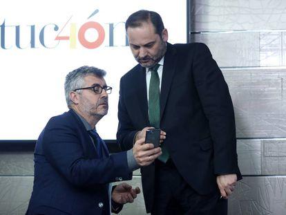 El secretario de Estado de Comunicación, Miguel Ángel Oliver, muestra su móvil al ministro de Fomento, José Luis Ábalos, en La Moncloa.
