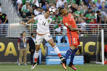 Chicharito y Vidal saltan a por un balón.