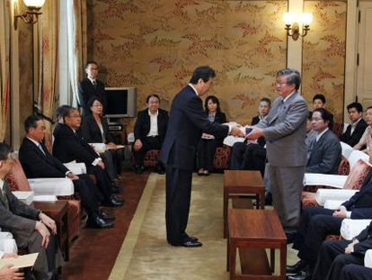 El portavoz del Parlamento japonés, Takahiro Yokomichi (a la derecha), recoge el informe sobre el accidente en la central nuclear de Fukushima.