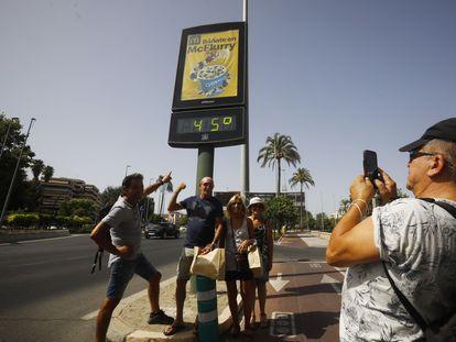 Unos turistas se fotografían en una calle de Córdoba debajo de un termómetro que marca 45 grados, este jueves.