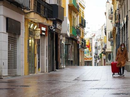 Una mujer camina por una calle vacía en Sevilla, el lunes.