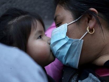 Una mujer migrante y un niño se besan durante una reunión para solicitar al gobierno de Chile regular su estatus migratorio antes de que se publique una nueva regla que facilite la expulsión del país, según medios locales, durante la pandemia, en Santiago, Chile, el12 de abril de 2021.