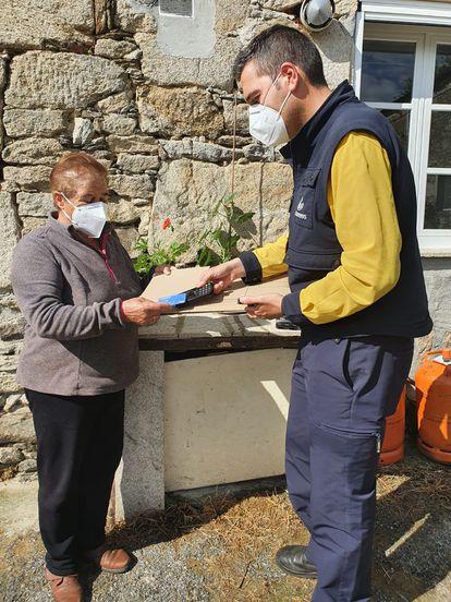 Un cartero rural cobra un servicio a una vecina de Friol (Lugo) con su PDA.