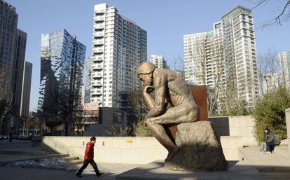 Un hombre pasa frente a una estatua en un distrito de negocios del centro de Pekín.