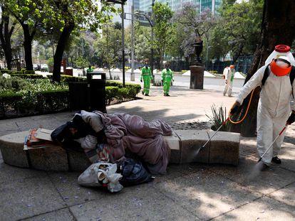 Un hombre duerme en un banco mientras un empleado del Gobierno desinfecta el área en Ciudad de México, el año pasado.