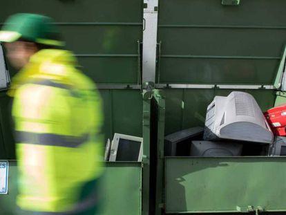 Un operario del punto limpio de la calle San Romualdo del distrito de San Blas, en Madrid, revisa los contenedores de residuos electrónicos.