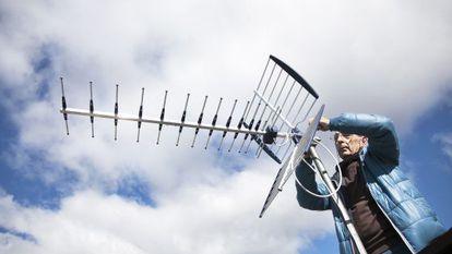 Un antenista cambia una antena y resintoniza los canales de TDT.