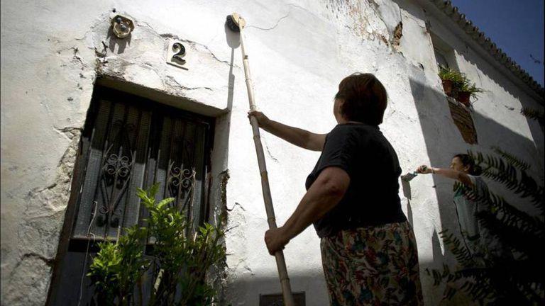 Manuela Delgado, vecina del pueblo gaditano de Medina Sidonia, encala la fachada de su casa en una imagen de archivo.