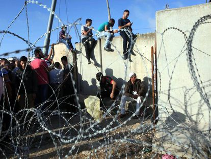 Un grupo de palestinos espera a pasar el puesto de control de Kalandia para visitar la mezquita Al-Aqsa durante el Ramadán en 2016.