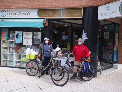 Elena Martínez con su padre, Víctor Martínez, con las bicicletas con las que han repartido los libros durante la cuarentena.