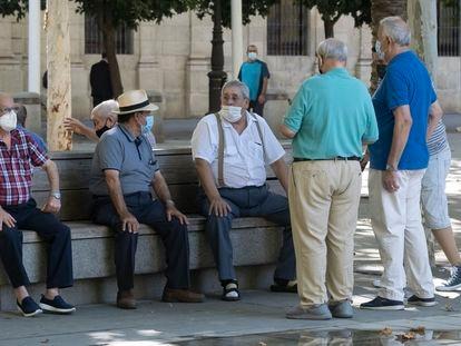 Un grupo de jubilados en un banco de un parque de Sevilla en septiembre de 2020.