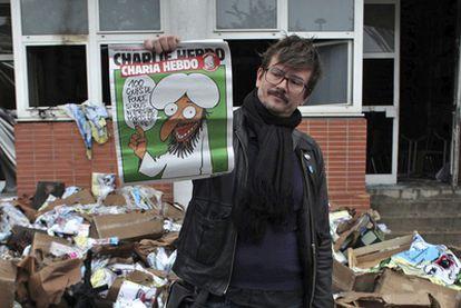 Un periodista muestra la portada del último ejemplar ante la sede de la redacción en París.