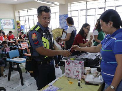 Un policía deposita su vota en la urna en Manila, Filipinas.