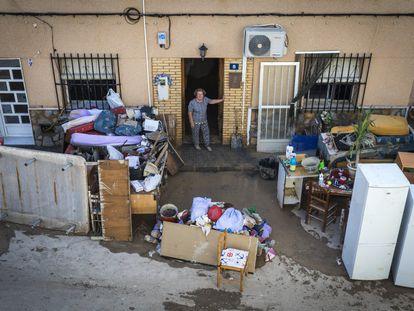 Una mujer se asoma a la calle donde se encuentran sus pertenencias tras las inundaciones en Orihuela en 2019.