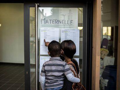 Una mujer busca información sobre la nueva clase de su hijo, en una escuela maternal en Lyon (Francia), en 2014.