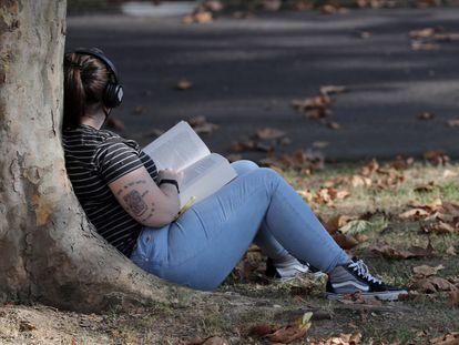 Una mujer lee un libro en un parque en Bilbao.