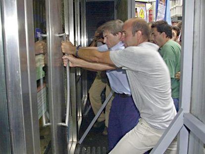 Argentinos intentan romper la puerta de un banco para entrar en él, en Buenos Aires, en febrero de 2002.