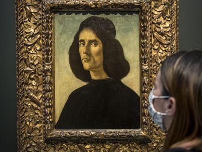 """Una persona observa el 'Retrato de Michele Marullo Tarcaniota"""", de Sandro Botticelli, que ha sido presentado este martes en el Museo de Bellas Artes de Valencia."""
