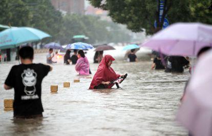 Gente caminando por una carretera inundada de Zhengzhou, en la provincia central china de Henan, el martes 20 de julio de 2021.