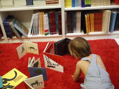 Un niño juega con libros infantiles en una librería.