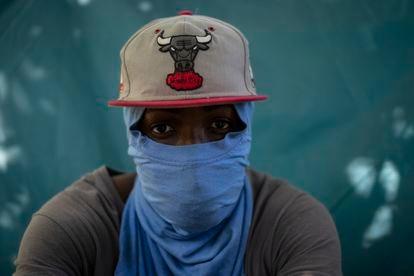 Wilson Joseph cubre su rostro con una camiseta frente a la tienda de campaña donde duerme en Ciudad Acuña.