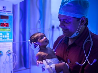 El doctor Rakh sostiene a una de sus recién nacidas.