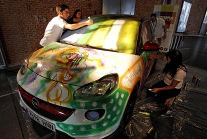 Intervención artística de voluntarios sobre un coche expuesto en la feria.