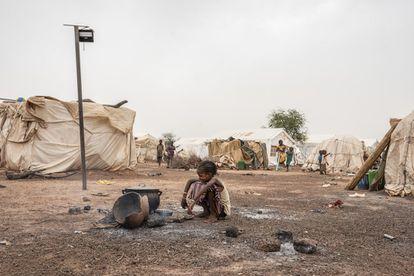 Una niña, frente a una cacerola puesta sobre el fuego en un campo de desplazados por la violencia en Barsalogho, Burkina Faso.