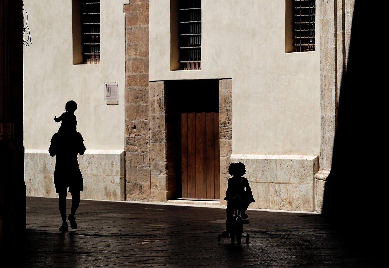 Un hombre pasea por el centro de Valencia junto a dos niños, en el 45º día de confinamiento.