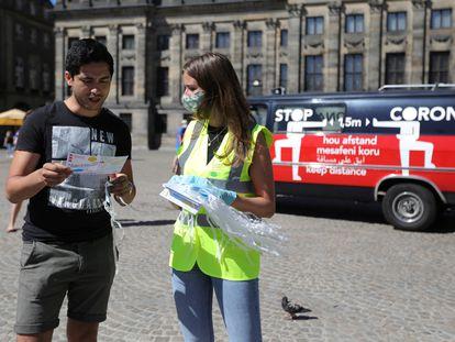 Una joven reparte mascarillas y folletos informativos sobre su uso en las calles de Ámsterdam.
