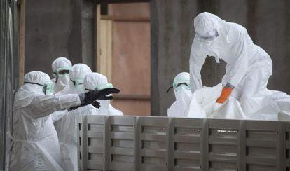 Varias enfermeras en Liberia con trajes de aislamiento preparan cadáveres de víctimas del ébola para su enterramiento.