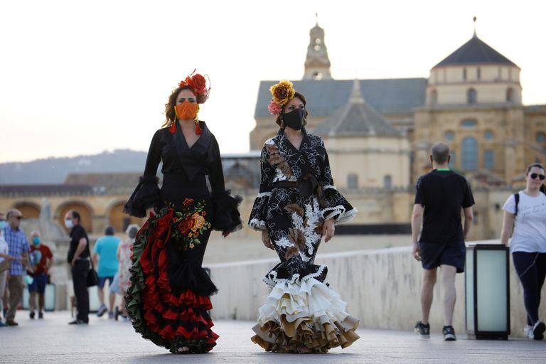 Dos mujeres protegidas con máscaras sanitarias y vestidas de flamencas dan un paseo por las calles de Córdoba, este viernes.