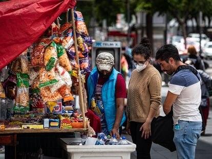 Una pareja compra bebidas en un puesto callejero de Ciudad de México, el 07 de Agosto de 2020. FOTO: Nayeli Cruz