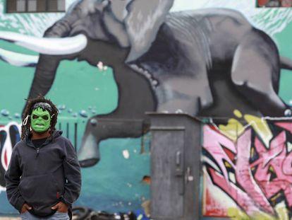 Un hombre con una máscara frente a un graffiti en Woodstock, un suburbio de Ciudad del Cabo.