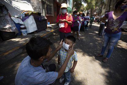 Un hombre le pone una mascarilla a su hijo mientras espera recibir comida de forma gratuita en Ciudad de México.