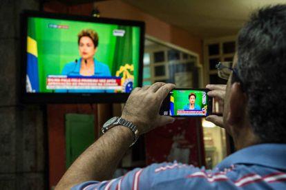 Un hombre graba en Brasil un discurso televisado de Roussef.
